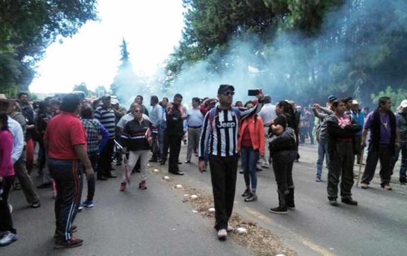 El Gobierno de Michoacán envió al lugar a 120 agentes antimotines para reabrir la vialidad, lo que desató un enfrentamiento con piedras, palos y gases lacrimógenos