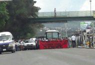 """Los manifestantes portan una manta de color rojo con negro con la siguiente leyenda: """"Vivos de los llevaron vivos los queremos"""""""