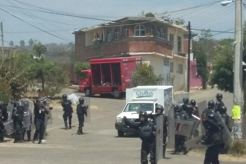 Los manifestantes se trasladaron a la carretera, donde incendiaron dos vehículos de empresas comerciales y una patrulla, por lo que los oficiales comenzaron a replegarlos hacia las instalaciones de la Escuela Normal
