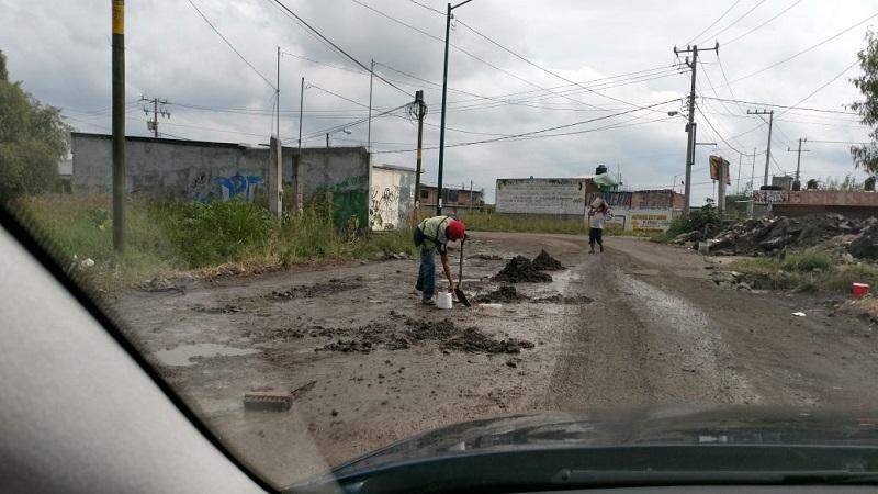 Ante la inoperancia de las autoridades municipales, ciudadanos de manera voluntaria se han puesto a tapar los baches con tierra y escombros; a cambio piden cooperación de los automovilistas (FOTOS: FRANCISCO ALBERTO SOTOMAYOR)