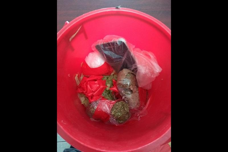 La cubeta tenía doble fondo y en el interior tenía tres envoltorios con cinta roja, uno de ellos contenía sustancia color blanca con las características propias a la droga conocida como cristal, mientras los otros dos vegetal verde seco de las características propias a la marihuana