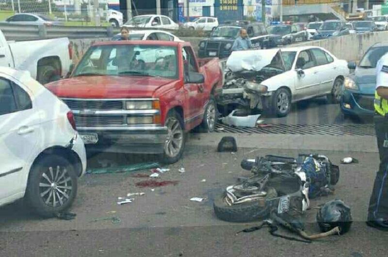 Entre dos de los vehículos quedó una motocicleta marca Italika, de color negro y azul con placas de Estado de México, resultando severamente lesionado el conductor